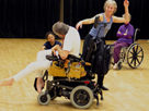 Picture of man in wheelchair dancing with woman who is on her feet.
