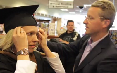 blonde woman puts on graduation cap and gown