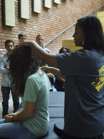 Melissa Polk, medical student at Touro University, gives a demonstration of osteopathic manipulative medicine at recent PHAP symposium. By: Jill Hardeman