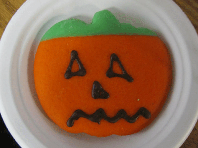 Cookie decorated like a pumpkin.