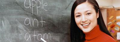 Woman holding chalk next to chalk board