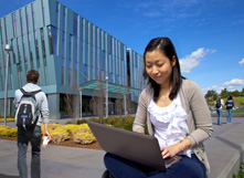 Female Asian student at laptop outside SSA building on Hayward campus
